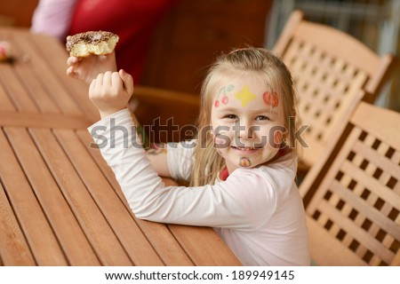 Picture of funny little girl with colorful donuts - stock photo