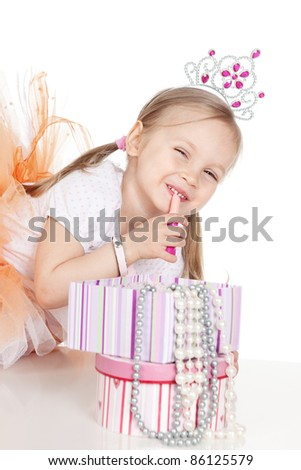 Picture of funny little girl with lipstick and accessories over white - stock photo