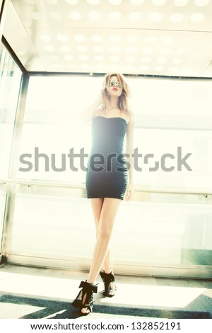 picture of girl in sunglasses posing in elevator - stock photo