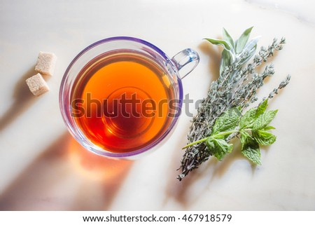 Picture of glass cup with tea, herbs and sugar on marble surface.