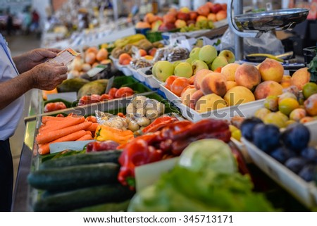 Picture of grocery stall with various fresh fruits and vegetables and man making purchases.  - stock photo