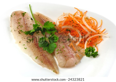 Picture of hake tenderloin with onion and carrot on a white plate - stock photo
