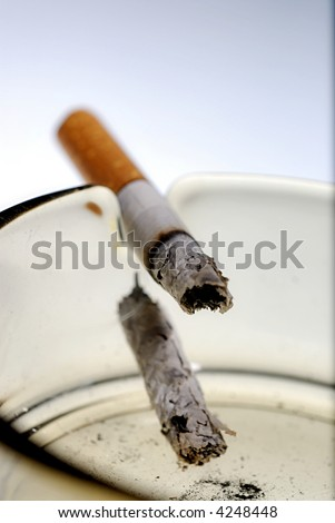 Picture of half burned cigarette in ash tray.