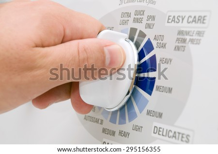Picture of hand turning the time dial on a top load washing machine