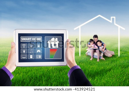 Picture of hands holding tablet with smart house controller applications on the screen. Shot with young man and his children reading book under a house symbol - stock photo
