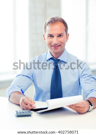 picture of handsome businessman with notebook and calculator - stock photo