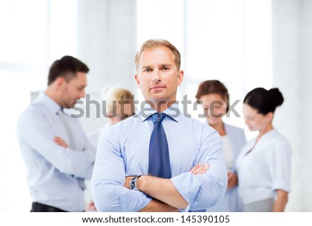picture of handsome businessman with team in office - stock photo