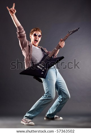 Picture of handsome guitarist in sunglasses making a rock gesture - stock photo