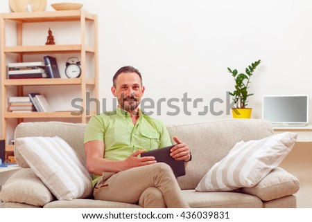 Picture of handsome man using tablet PC at home and looking at camera. Happy man working from home. Man sitting on sofa or couch. - stock photo