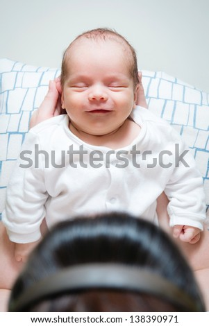 picture of happy adorable baby resting in his mamas hands - stock photo
