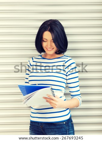 picture of happy and smiling teenage girl with big notepad - stock photo
