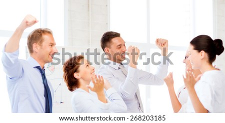 picture of happy business team celebrating victory in office - stock photo