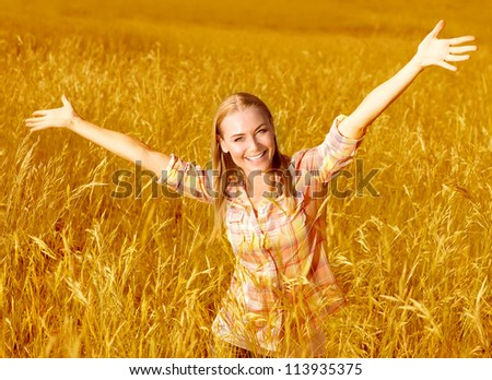 Picture of happy cheerful girl having fun on wheat field, beautiful blond woman with raised up hands enjoying freedom outdoors, agriculture lifestyle, autumn harvest concept, fall season - stock photo