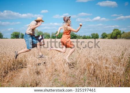 Picture of happy couple having fun in wheat field. Excited young man and woman running with old suitcase on blue sky outdoor background.  - stock photo