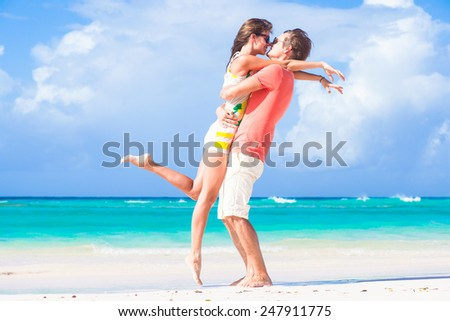 picture of happy couple in sunglasses hugging on the beach - stock photo