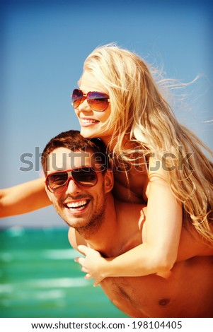 picture of happy couple in sunglasses on the beach, focus on man - stock photo