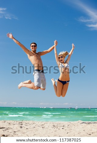 picture of happy couple jumping on the beach. - stock photo