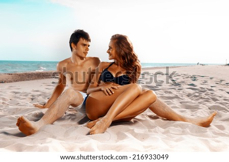 picture of happy couple sitting on the beach - stock photo