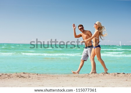 picture of happy couple walking on the beach. - stock photo