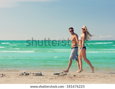 picture of happy couple walking on the beach