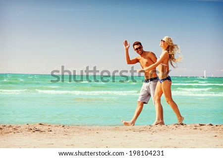 picture of happy couple walking on the beach - stock photo