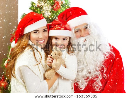 Picture of happy family celebrating New Year eve, little baby girl with parents enjoying winter holidays, father wearing red Santa Claus costume, Christmas magic, happiness and love concept - stock photo