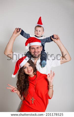 Picture of happy family celebrating New Year, little baby boy with parents and sister enjoying winter holidays, all red Santa Claus hat, Christmas magic, happiness and love concept