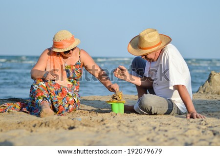 picture of happy mature couple, man & woman, having fun playing at seashore with children toys on sandy beach summer sea outdoors background  - stock photo