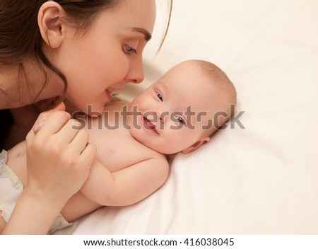 Picture of happy mother with adorable baby lying on bed - stock photo
