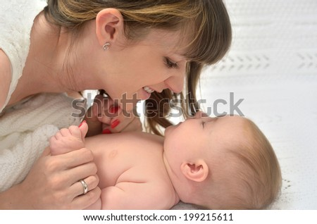 picture of happy mother with adorable baby playing on soft blanket