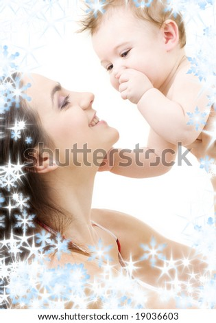picture of happy mother with baby and snowflakes (focus on baby) - stock photo