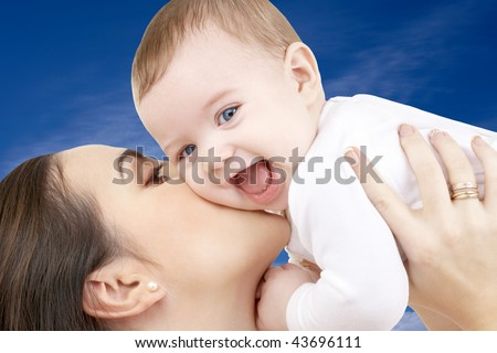 picture of happy mother with baby boy over blue sky - stock photo