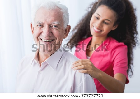 Picture of happy positive senior and afroamerican caregiver - stock photo