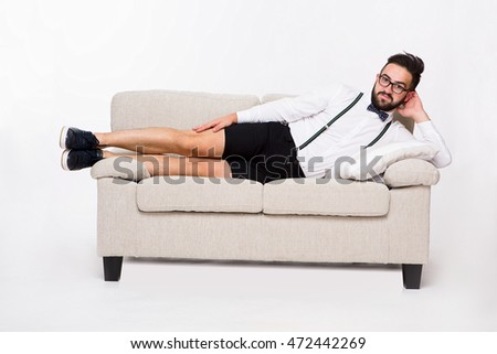 Picture of happy smiling handsome hipster man lying on couch or sofa in studio. Bearded man in shirt and shorts looking at camera. Emotions concept.