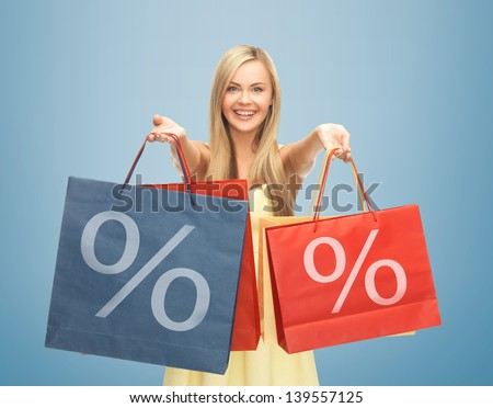 picture of happy woman holding shopping bags with percent sign - stock photo