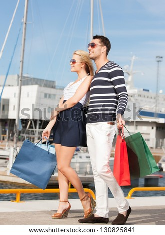 picture of happy young couple with shopping bags - stock photo