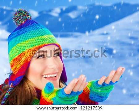 Picture of happy young woman catching snowflakes by hands, cheerful beautiful girl having fun in snowy mountains, attractive female wearing colorful wool hat and gloves, wintertime fashion, Christmas - stock photo