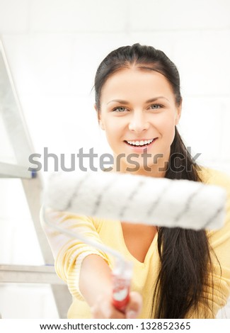 picture of happy young woman with paintroller - stock photo