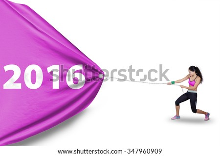 Picture of healthy indian woman wearing sportswear and pulling a big flag with numbers 2016 in studio
