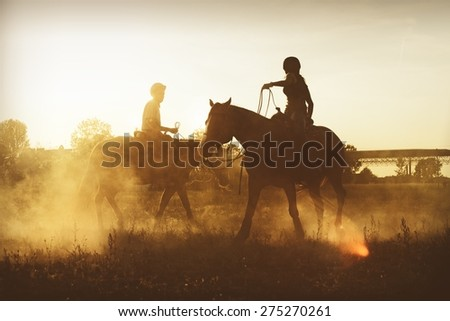 Picture of horseman riding a horse in the evening. - stock photo