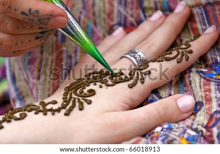 Picture of human hand being decorated with henna tattoo - stock photo