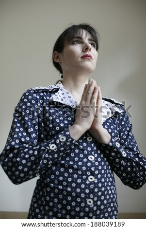 picture of image of young woman in dotted dress with prayer , woman with hands in prayer , image of young woman having prayer  - stock photo