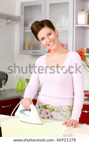 picture of ironing woman in the kitchen - stock photo