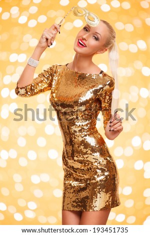 picture of joyful beautiful young woman in golden dress holding mask posing against gold background - stock photo