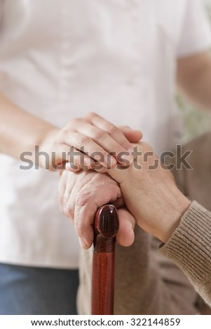 Picture of kind caregiver hand holding senior man hand - stock photo