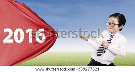 Picture of little business person pulling numbers 2016 with a big flag on the meadow - stock photo