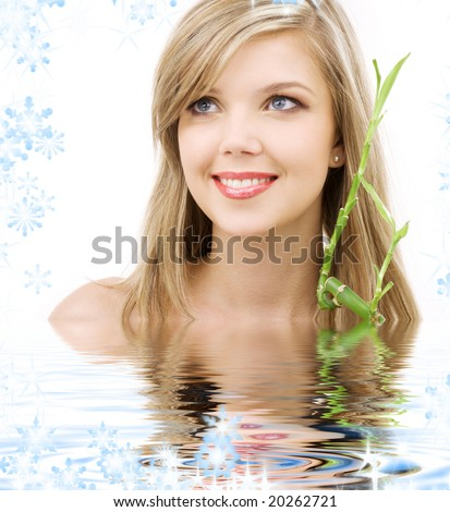 picture of lovely blue-eyed blonde with bamboo in water - stock photo