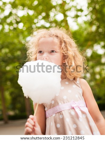 Picture of lovely girl eating cotton candy - stock photo