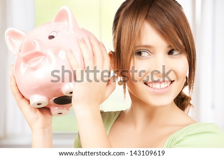 picture of lovely girl with big piggy bank - stock photo