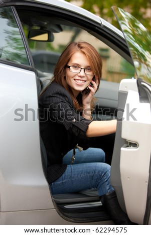 picture of lovely girl with cell phone in car - stock photo